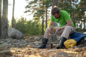 Caucasian man in hiking clothes uses wood to heat metal burner for cooking in forest in camp