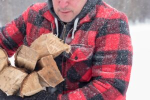 Man bringing in firewood in a snow storm