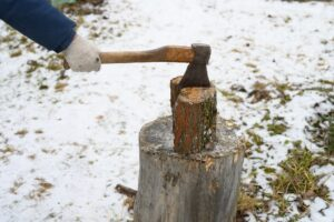 man's hand with an axe chopping wood