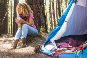 Pretty caucasian middle age woman sitting on the ground doing camping with tent in the forest